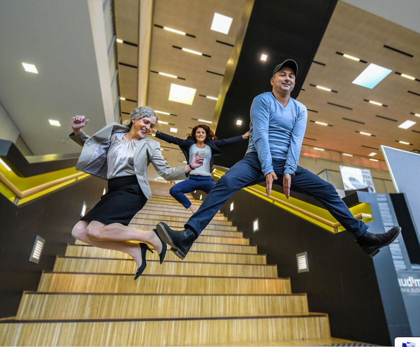 Three persons jumping off stairs